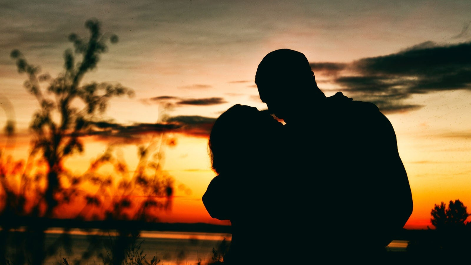 Silhouette of couple about to kiss at sunset