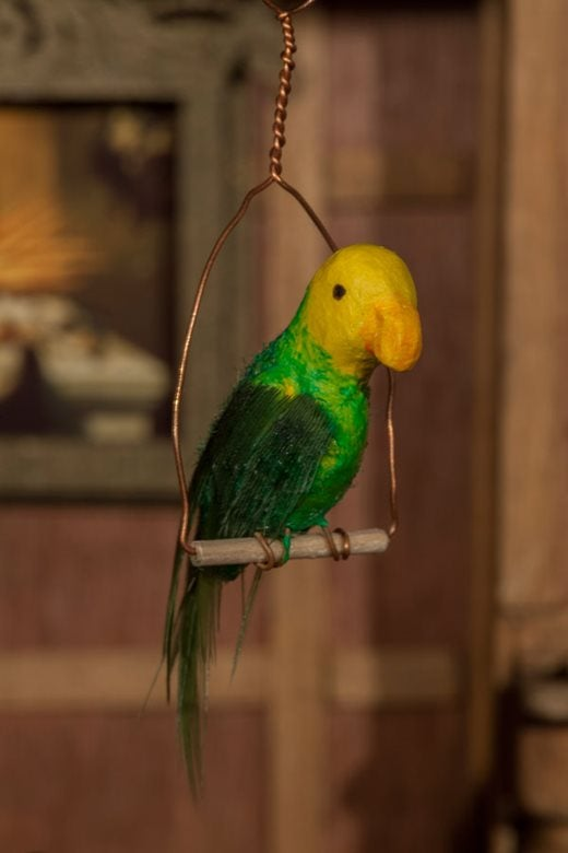 tiny version of a green and yellow parrot, complete with feathers, sitting on a perch