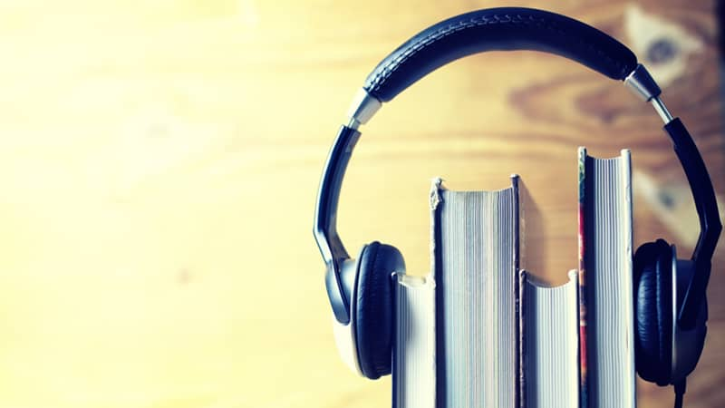 A pair of headphones looped over four books