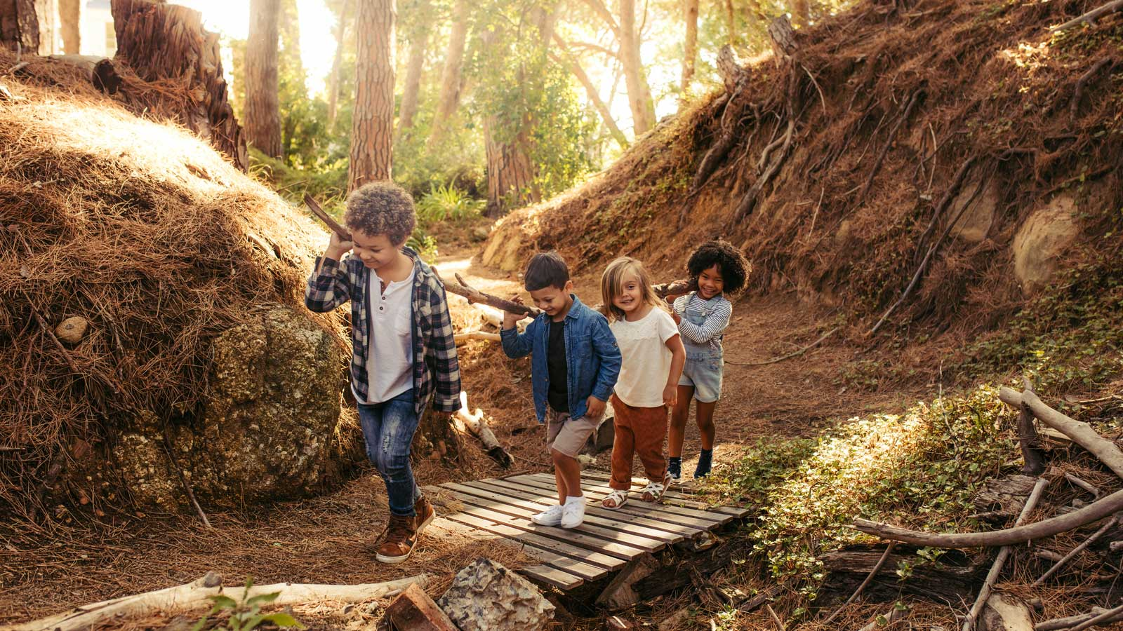Four children in a forest working together to carry a large log up a path