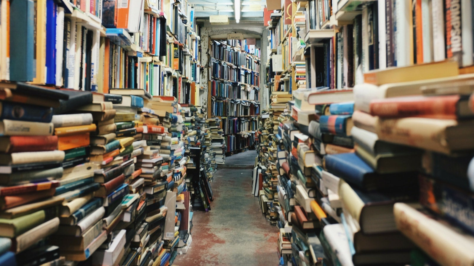 Corridor full of stacks of books in second hand bookshop