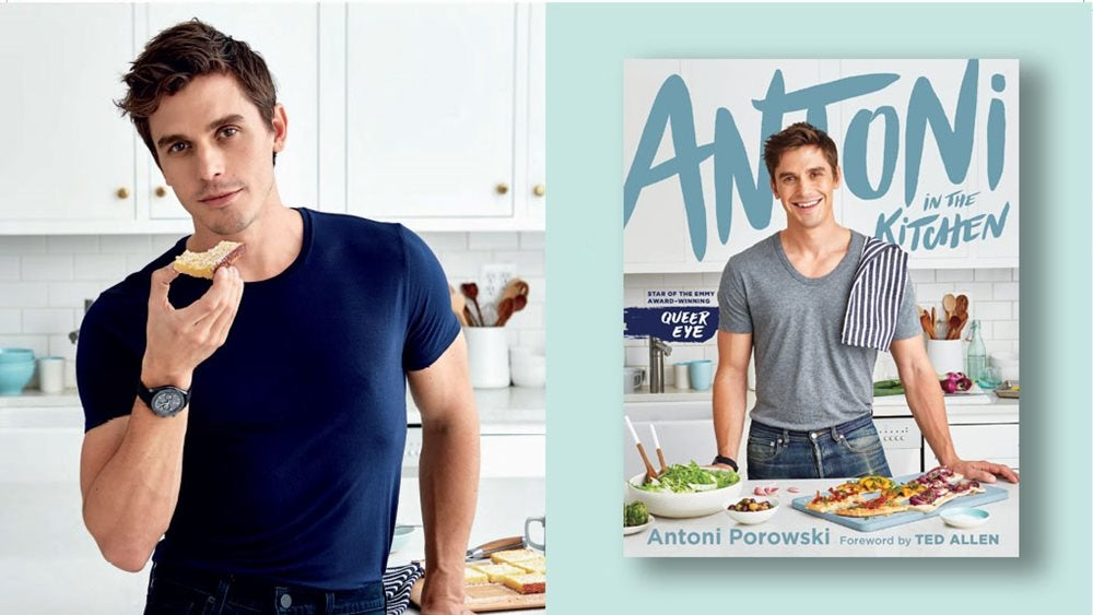 Antoni in a kitchen eating some bread alongside a copy of his book, Antoni in the Kitchen