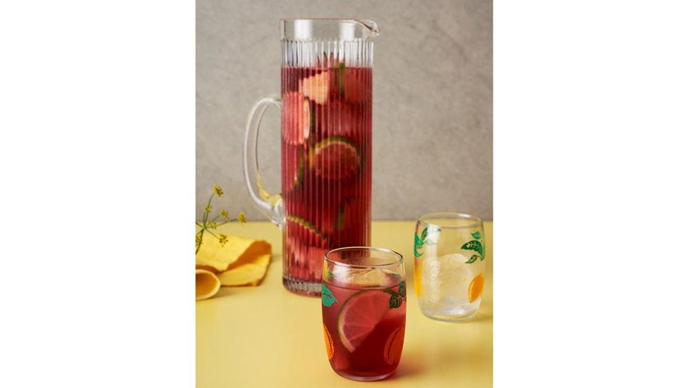 Jug and glass full of Agua de Jamaica cocktail