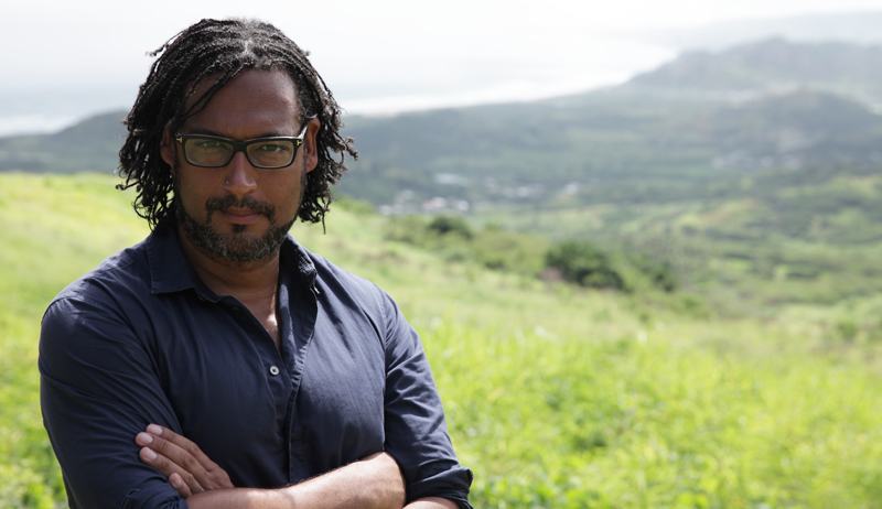 David Olusoga standing with arms folded in a field.