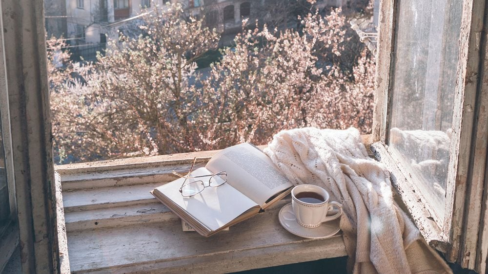 Book and coffee on windowsill with blossoms outside