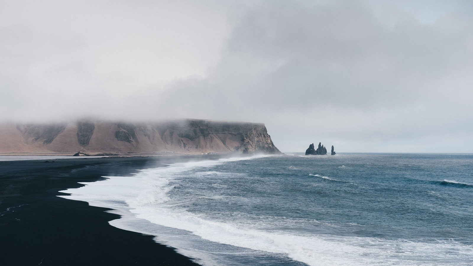 Icelandic beach with black sand and mist hanging over mountains in the far distance