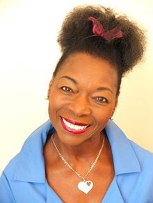 Photograph of Floella Benjamin smiling, wearing a blue shirt and a red bow in her hair