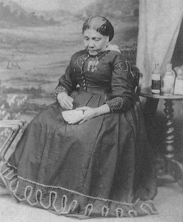 Black and white photograph of Mary Seacole, sitting tending to a small bowl, while wearing a fine dress with medals pinned to her chest