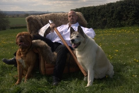 Author John Gwynne sitting on a fur-covered throne in a field, holding an axe with a large dog sitting on either side of him