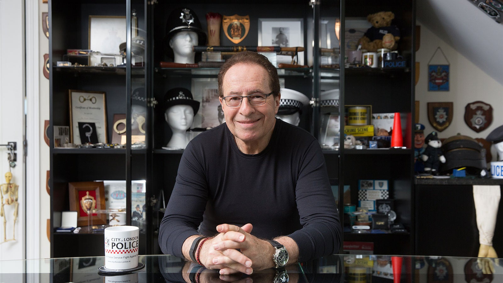 Peter James sat at a table surrounded by police memorabilia.