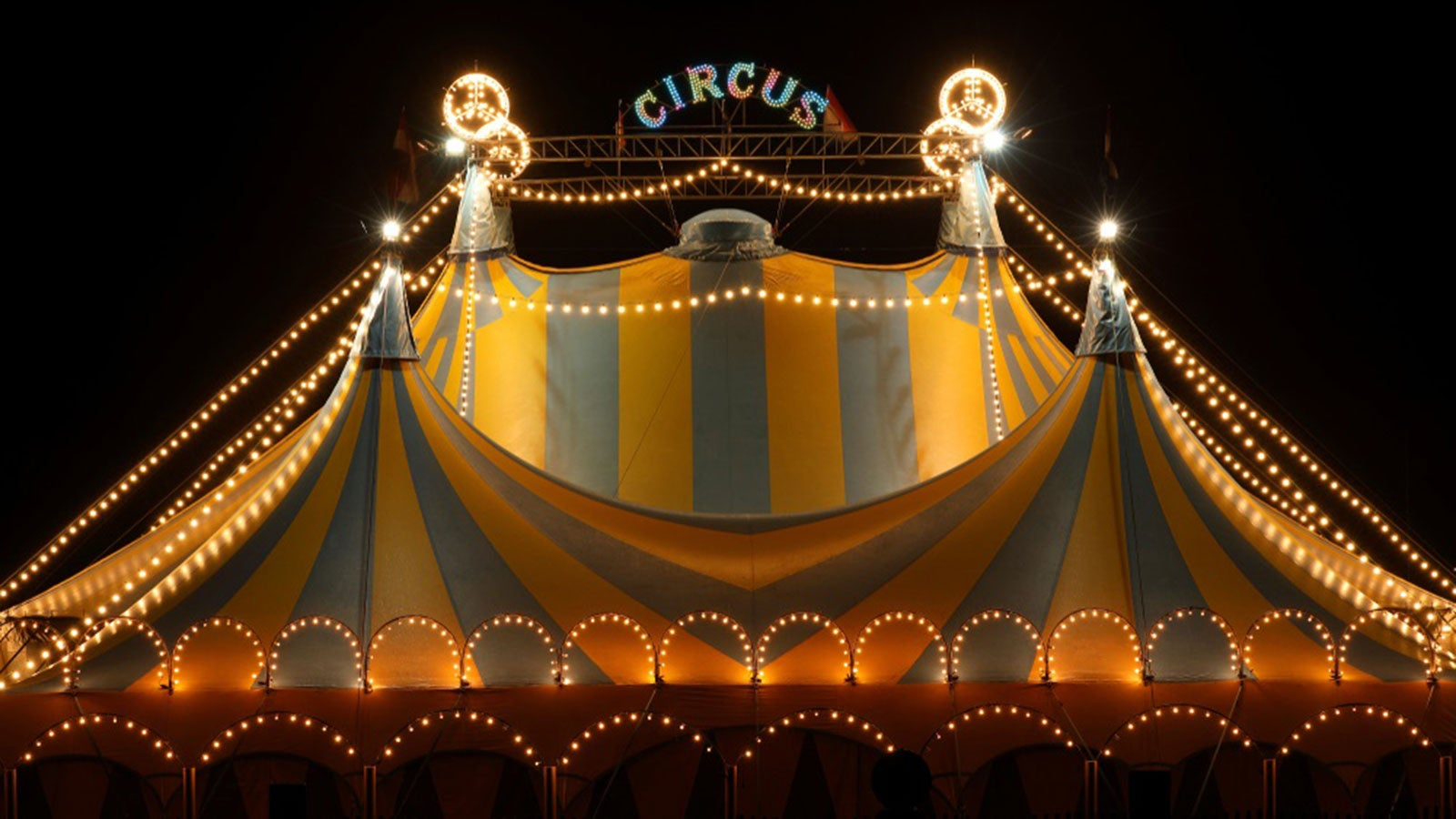 Blue and yellow circus tent with a light up circus sign on top at night