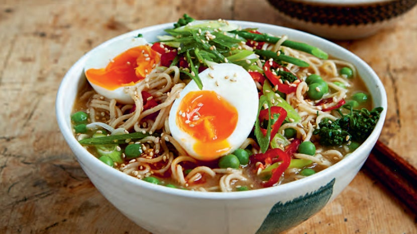 Close up photograph of ramen, showing noodles, brown broth, spring onions, chili peppers and a soft-boiled egg