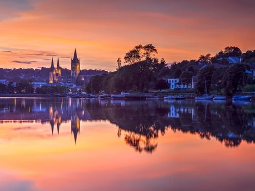 Truro at sunset, with a church lit up in the background and boats moored along the docks