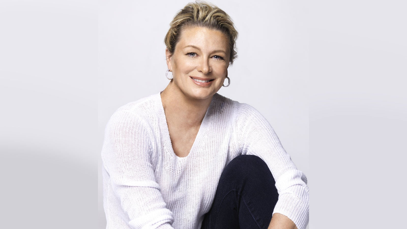 Kristin Hannah smiling wearing a white jumper in front of a white background