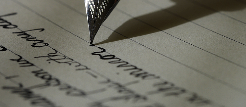 Close up of fountain pen pressed into paper with lines of text in black and white