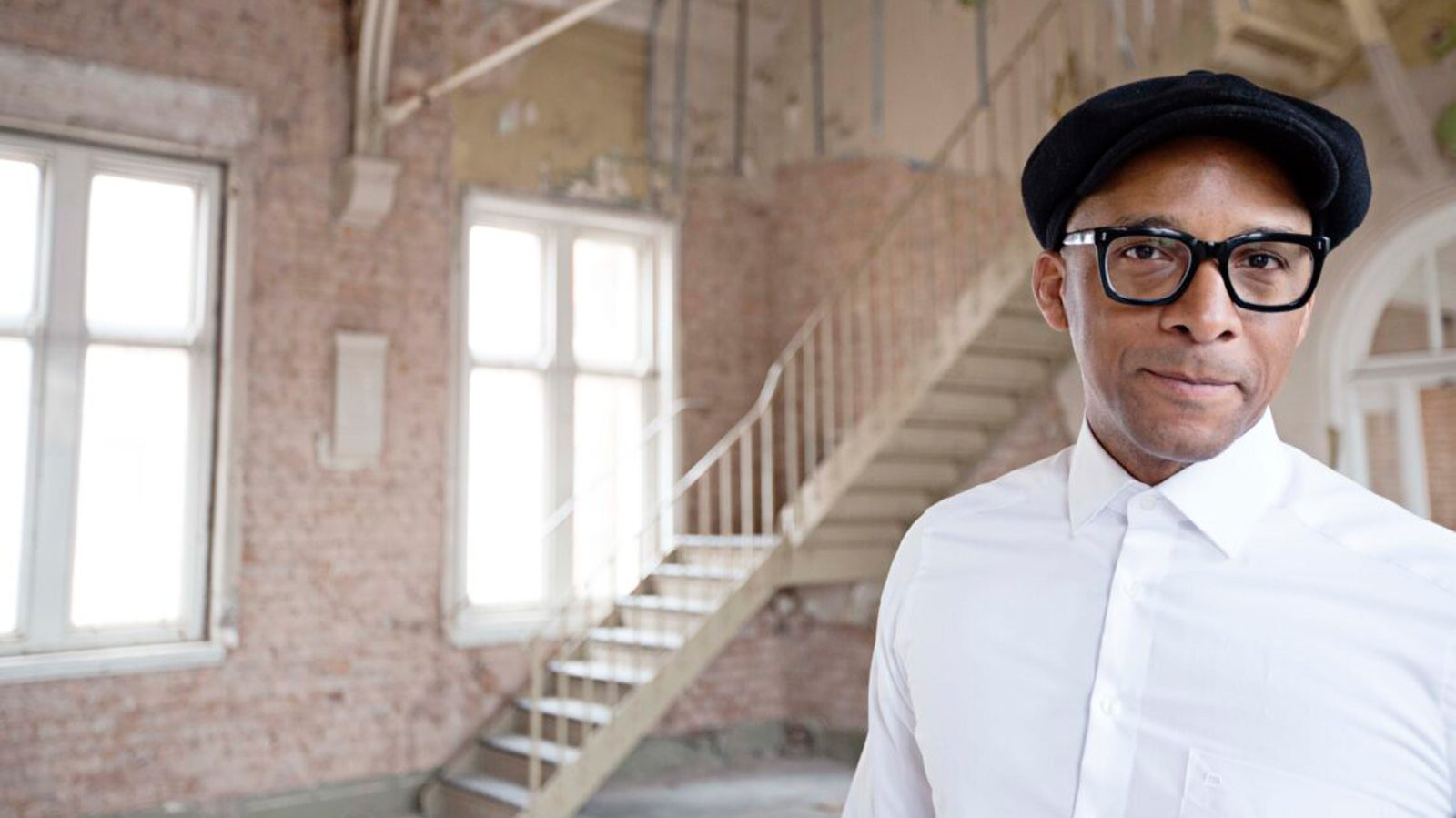 Jay Blades wearing a white shirt and black flatcap, smiling in a refurbished red-brick warehouse