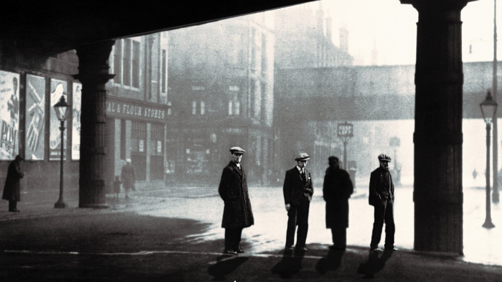 Black and white photograph of four men wearing wool coats and flat caps on the streets of 1930s Glasgow