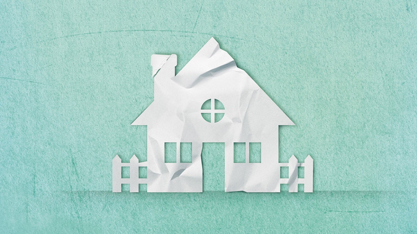 House with three windows, chimney and picket fence cut out of paper on a blue background