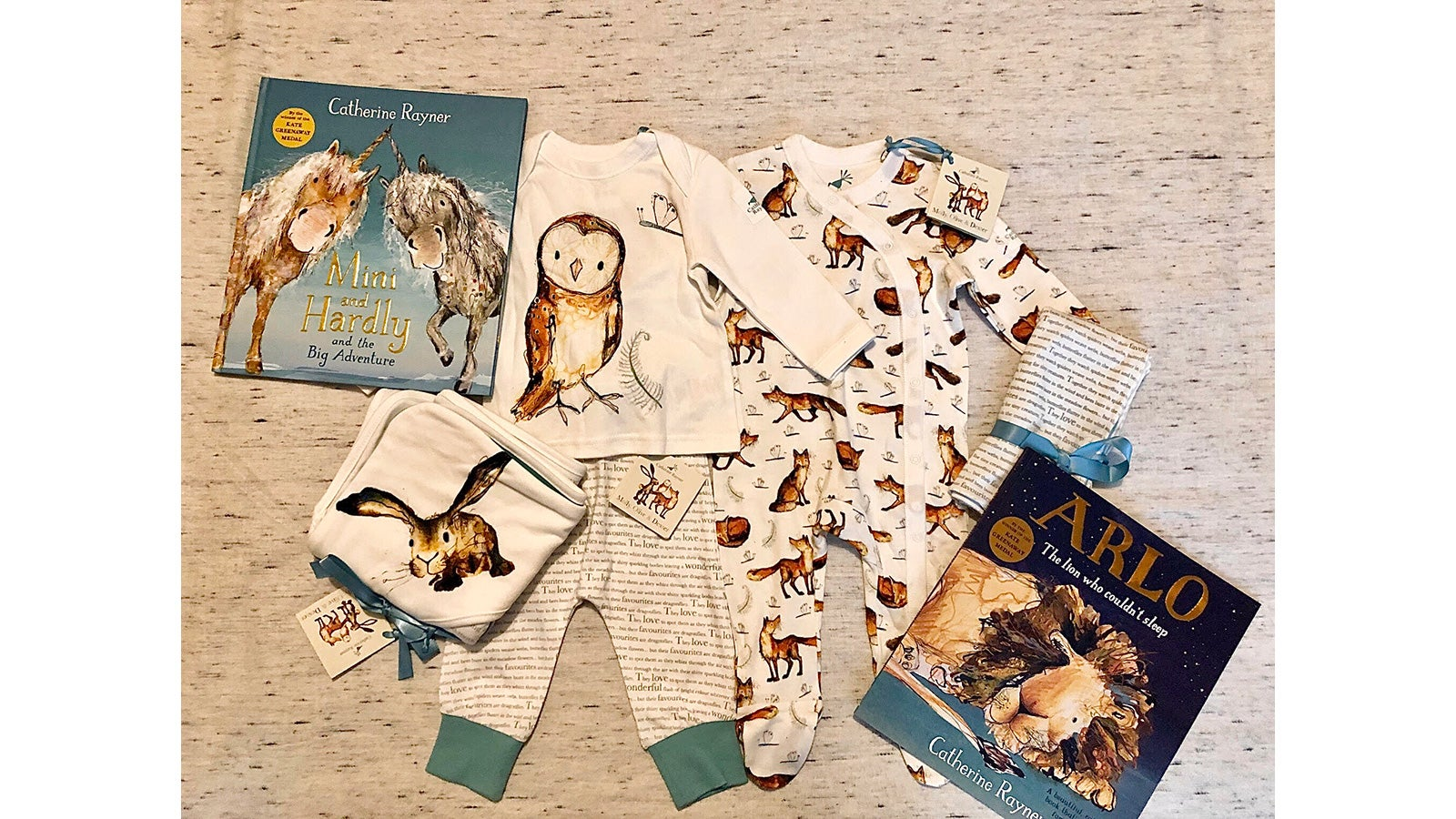 A bundle of babywear lies on a white patterned bedspread alongside a copy of Arlo the Lion Who Couldn't Sleep and Mini and Hardly and the Big Adventure