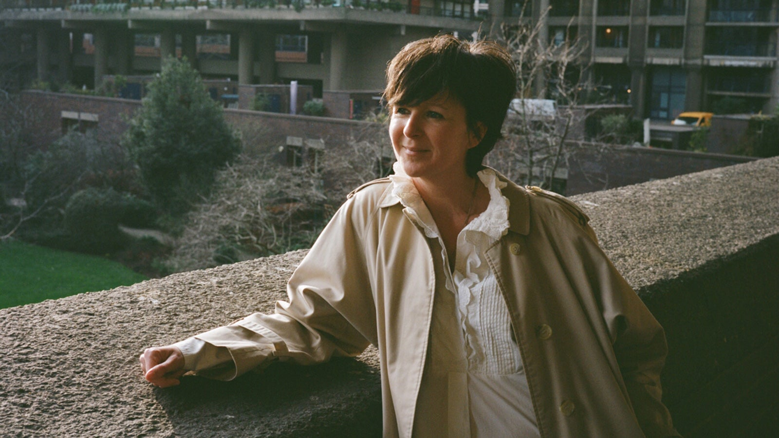Olivia Laing smiling leaning against a concrete balcony