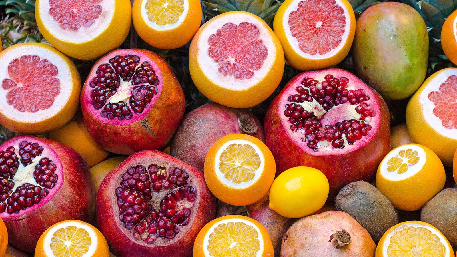 pomegranates oranges and grapefruit fill the image - some fruit have top cut off to show colourful seeds