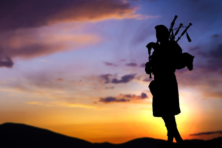 Silhouette of a man playing the bagpipes against the background of a sunset