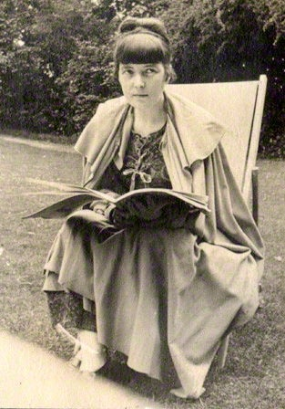 A black and whte photograph of Katherine Mansfield in 1917, sitting reading on a deck chair in a garden