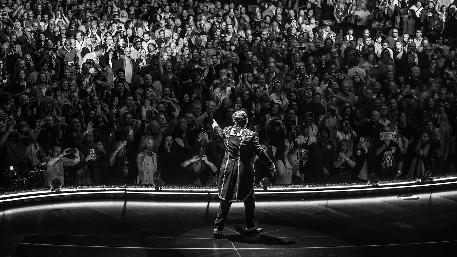 Black and white photograph of Elton John in front of a large crowd