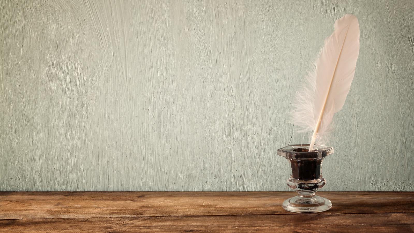 Glass ink pot with pink feather quill on wooden table