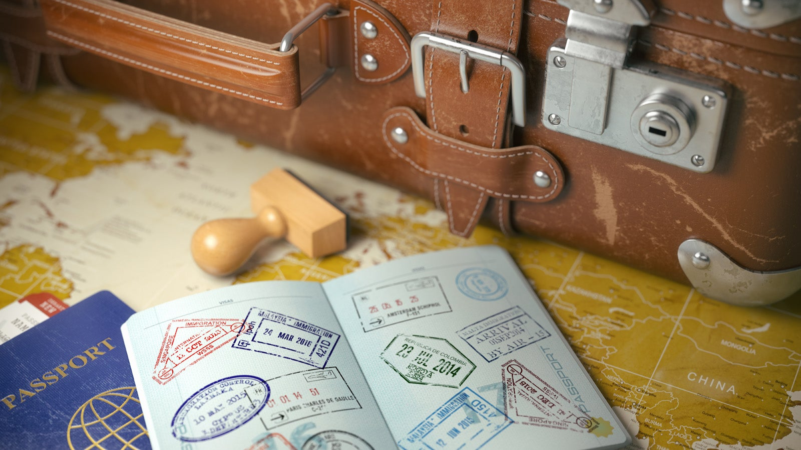A suitcase next to an open passport showing lots of stamps