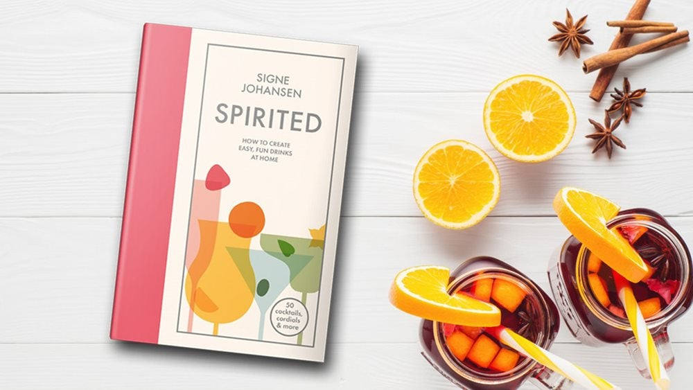 Spirited book next to two glasses of cocktails