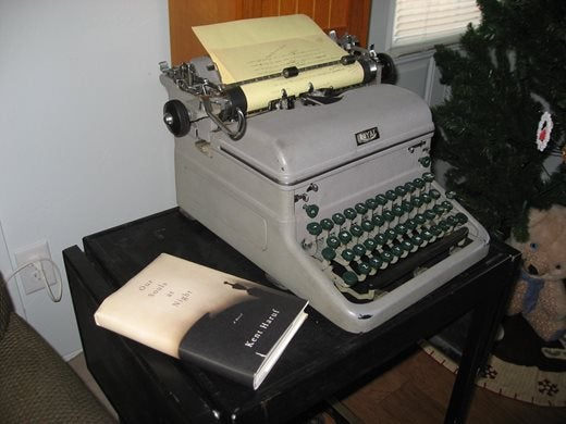 An old grey typewriter, with Kent's book Our Souls at Night sitting to the left of it