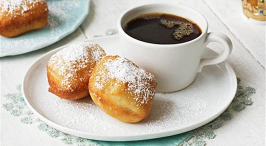 two beignets with cup of black coffee on plate