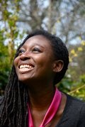 A photograph on Helen Oyeyemi smiling with woodland in the background