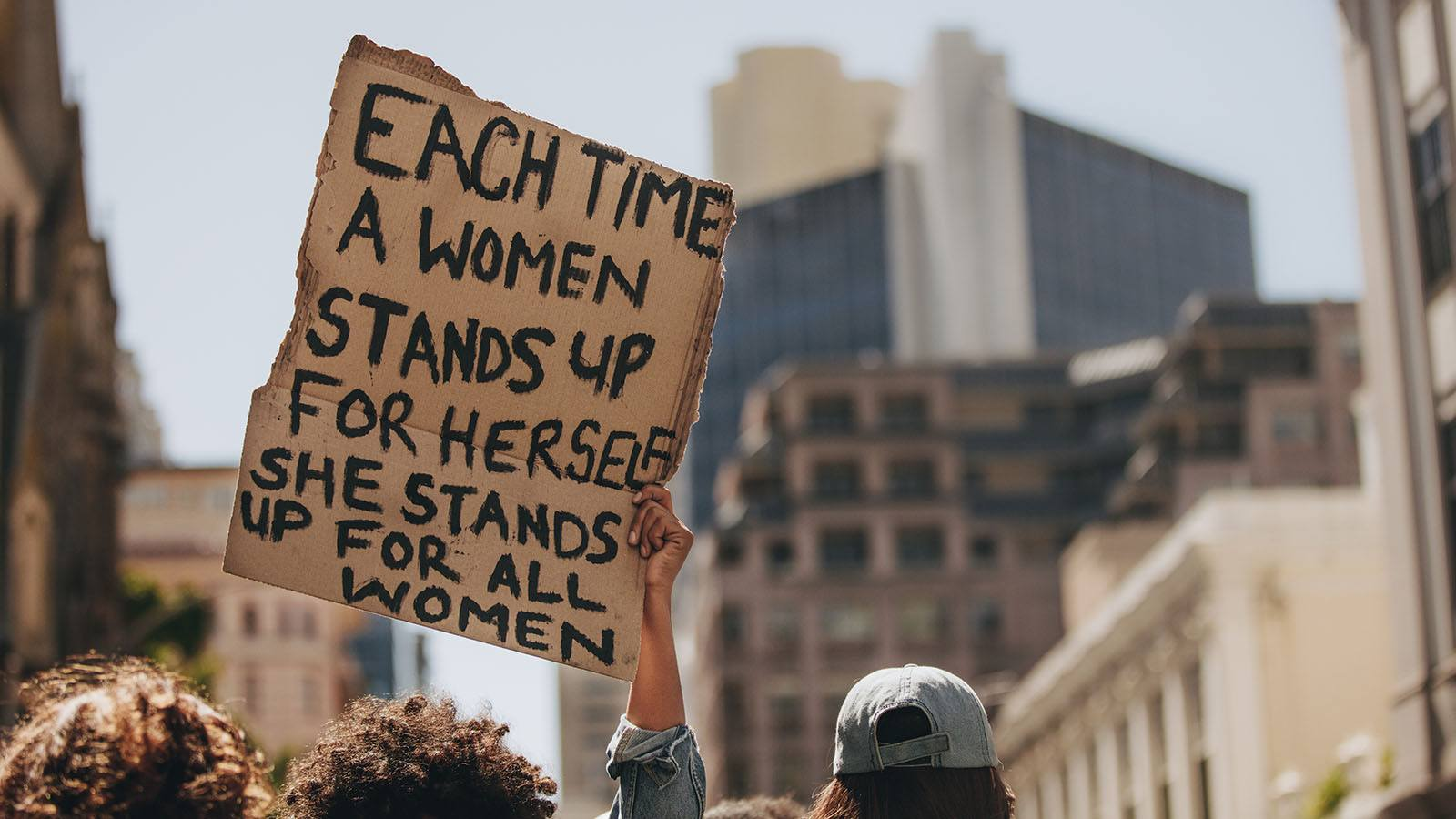 Image of a protest with a hand holding up a sign saying 'Each time a woman stands up for herself she stands up for all women.'