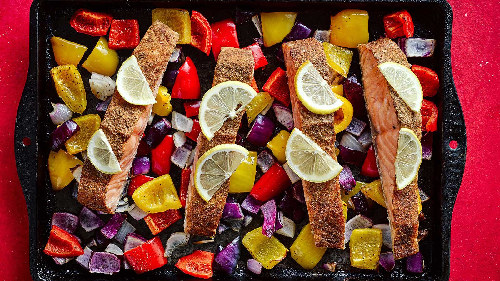 4 fillets of salmon surrounded by peppers, and red onion
