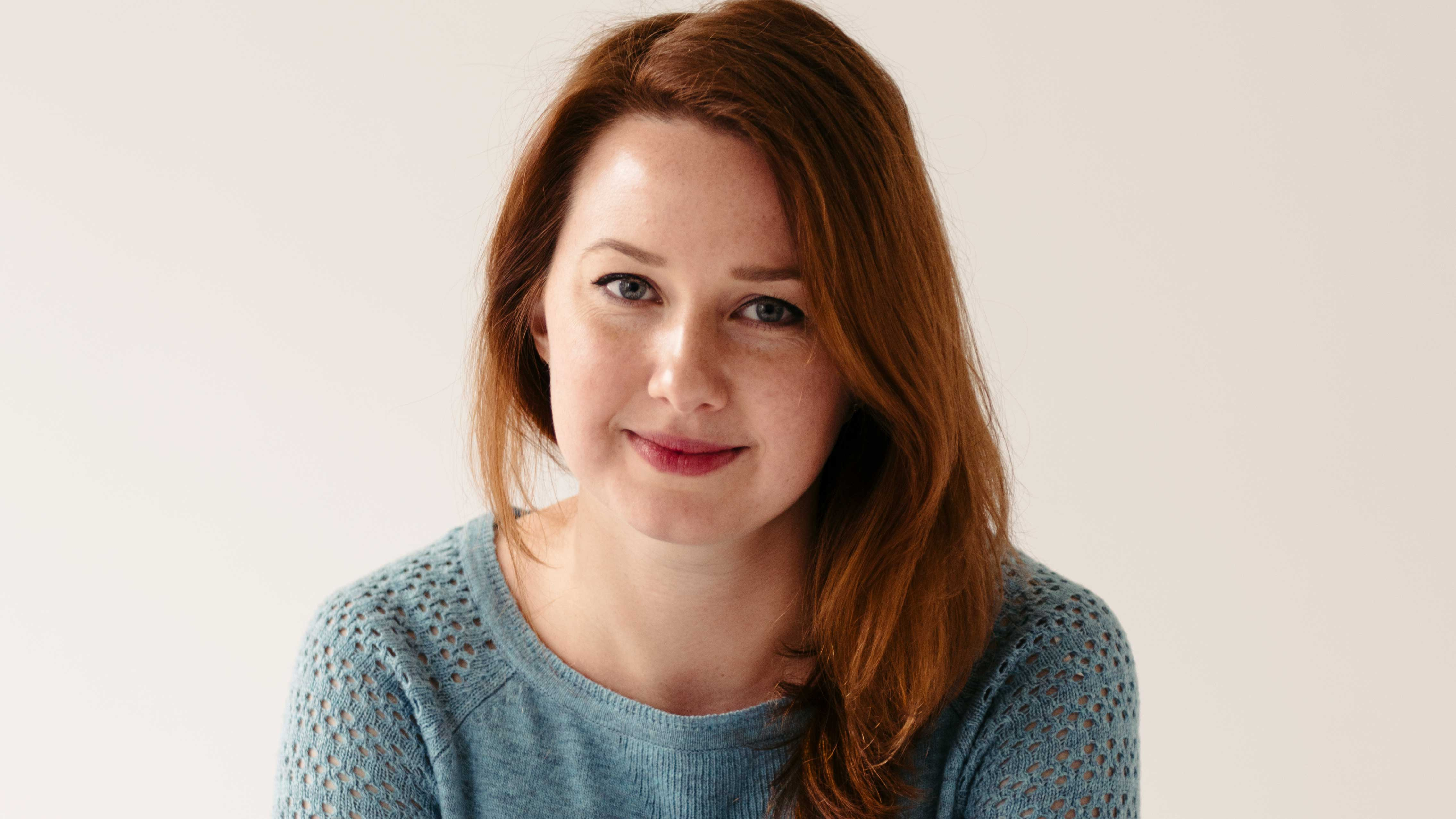 A photograph of Hannah Kent smiling at the camera wearing a blue jumper in front of a plain cream backdrop
