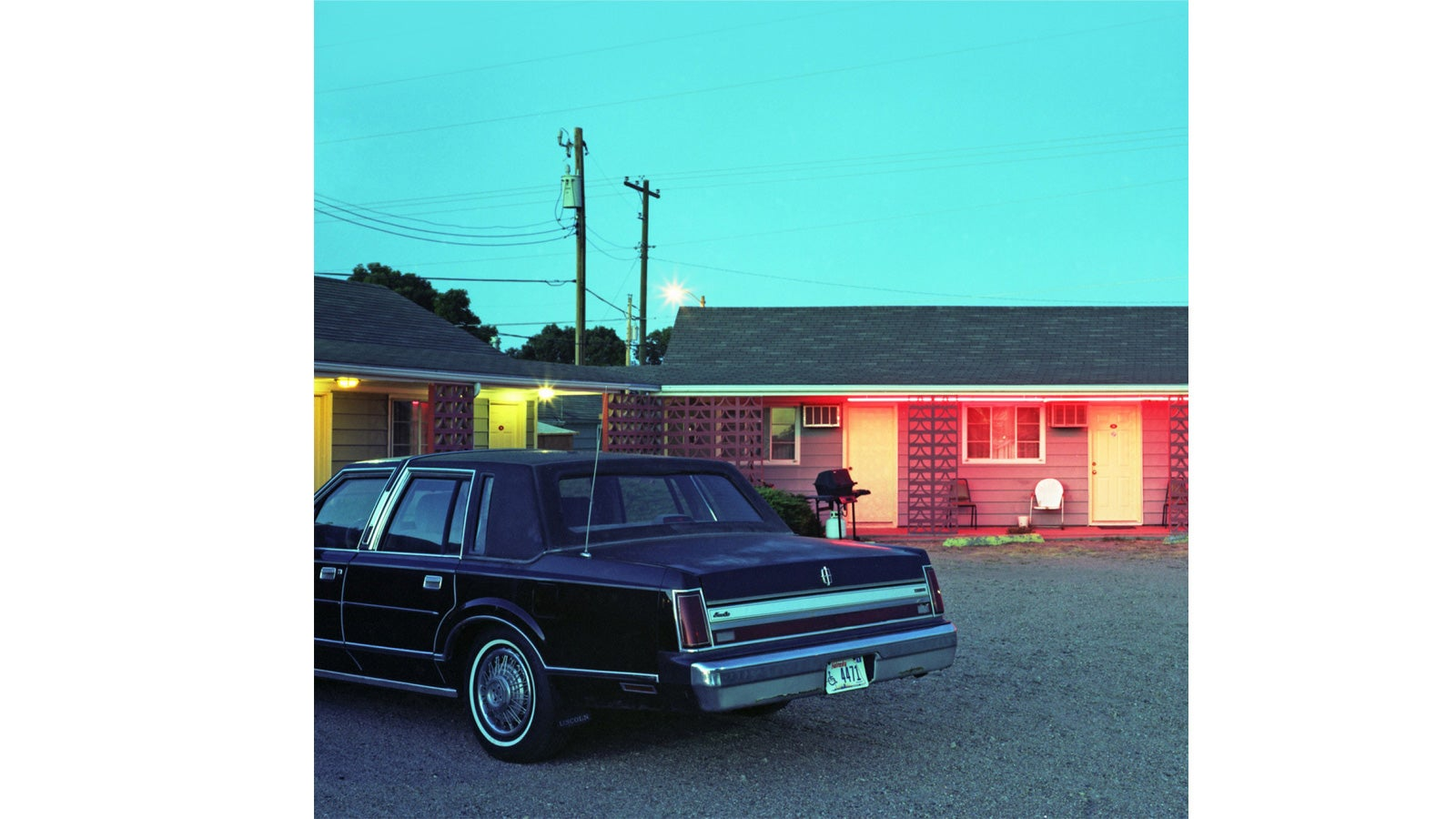 A vintage car in front of a motel at dusk