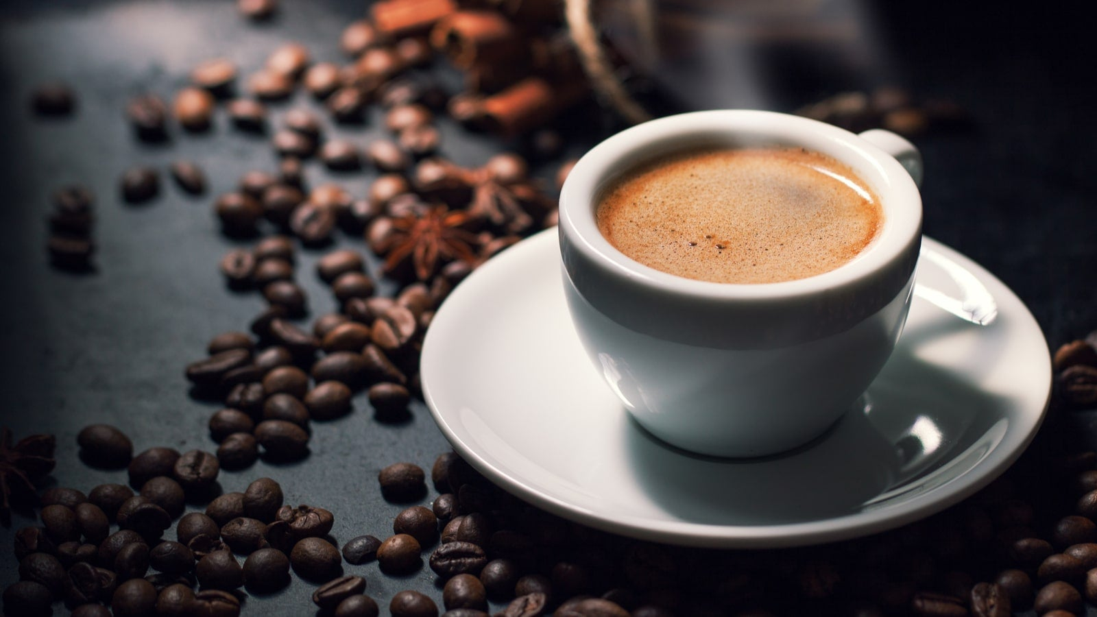 A hot cup of espresso surrounded by coffee beans
