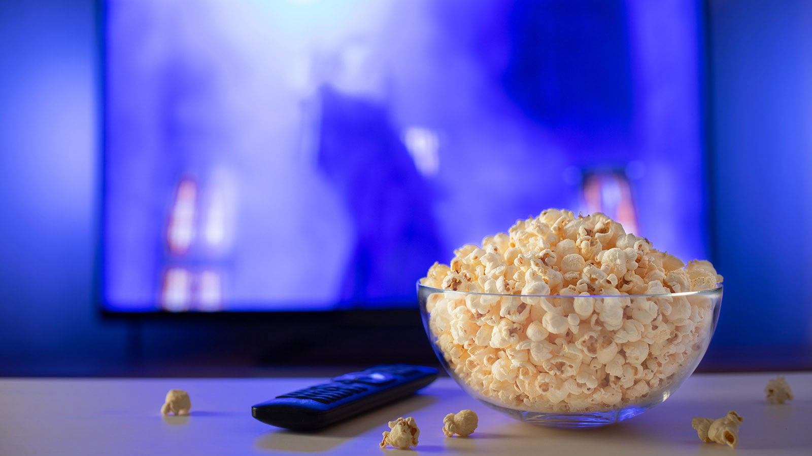 Bowl of popcorn and remote on table as film plays in background.