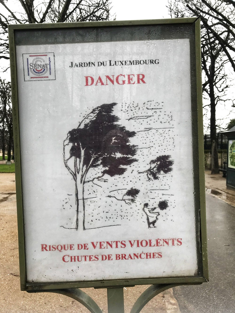 A sign warning about high winds in the Jardin du Luxembourg