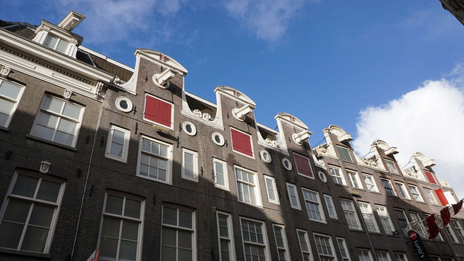 The tall houses above the shops of Kalverstraat with a blue sky above