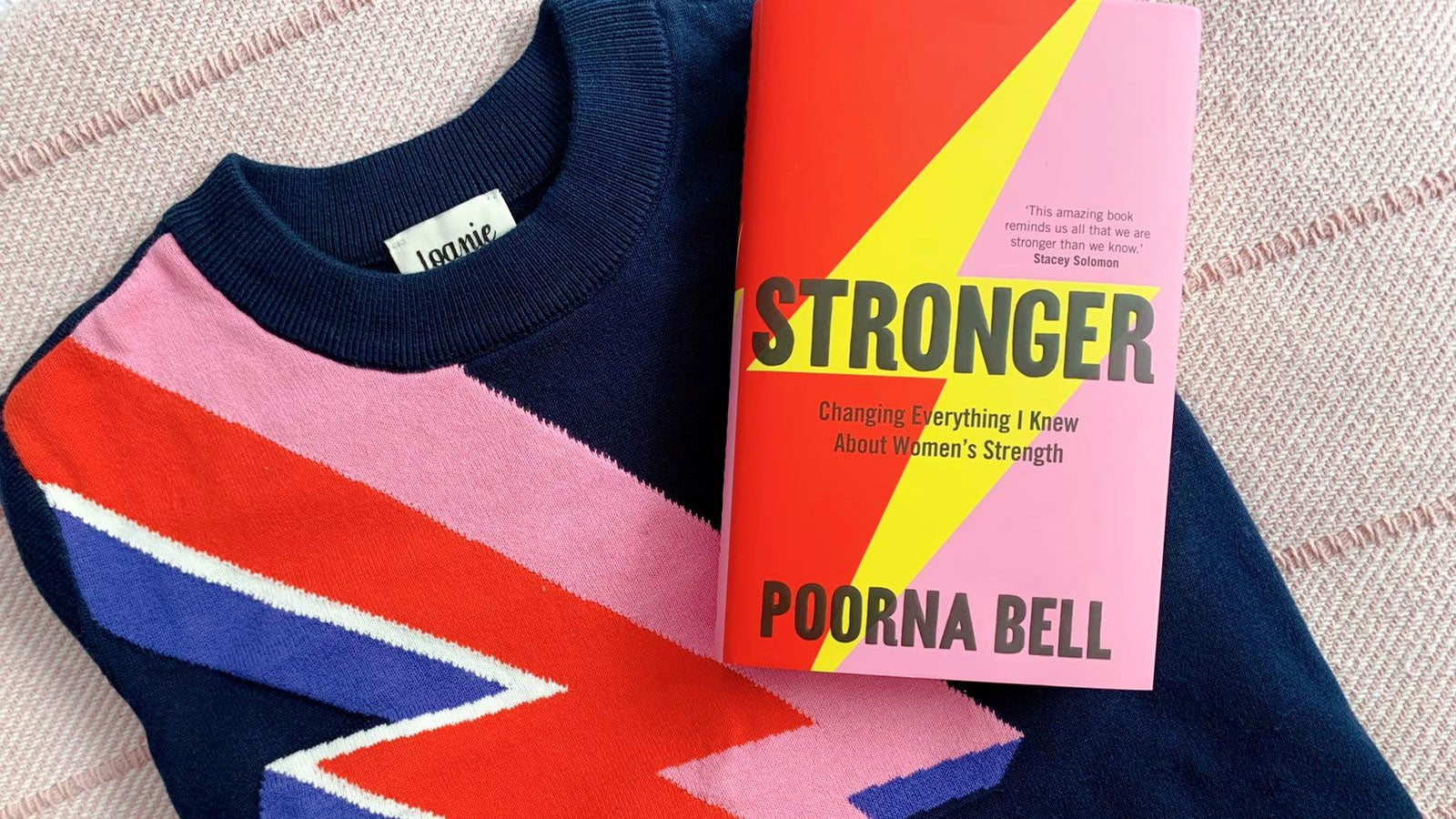 A copy of Poorna Bell's Stronger resting on a Joanie Clothing 'Kim Lightning Bolt Intarsia Jumper' on a striped bedspread.