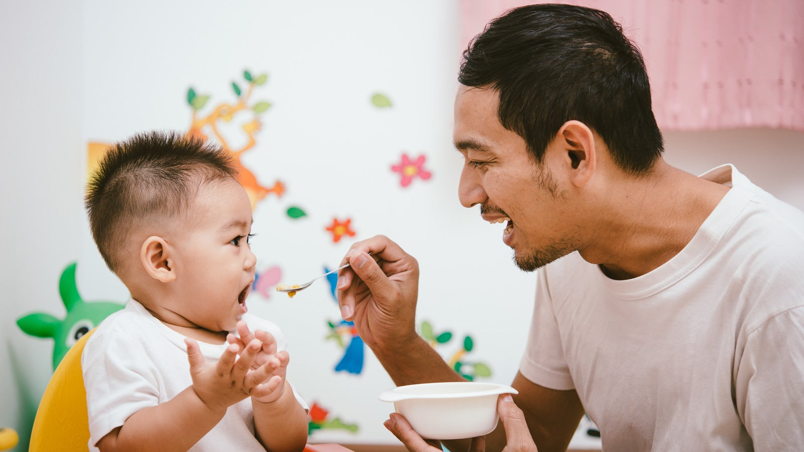 A smiling father feeding his toddler