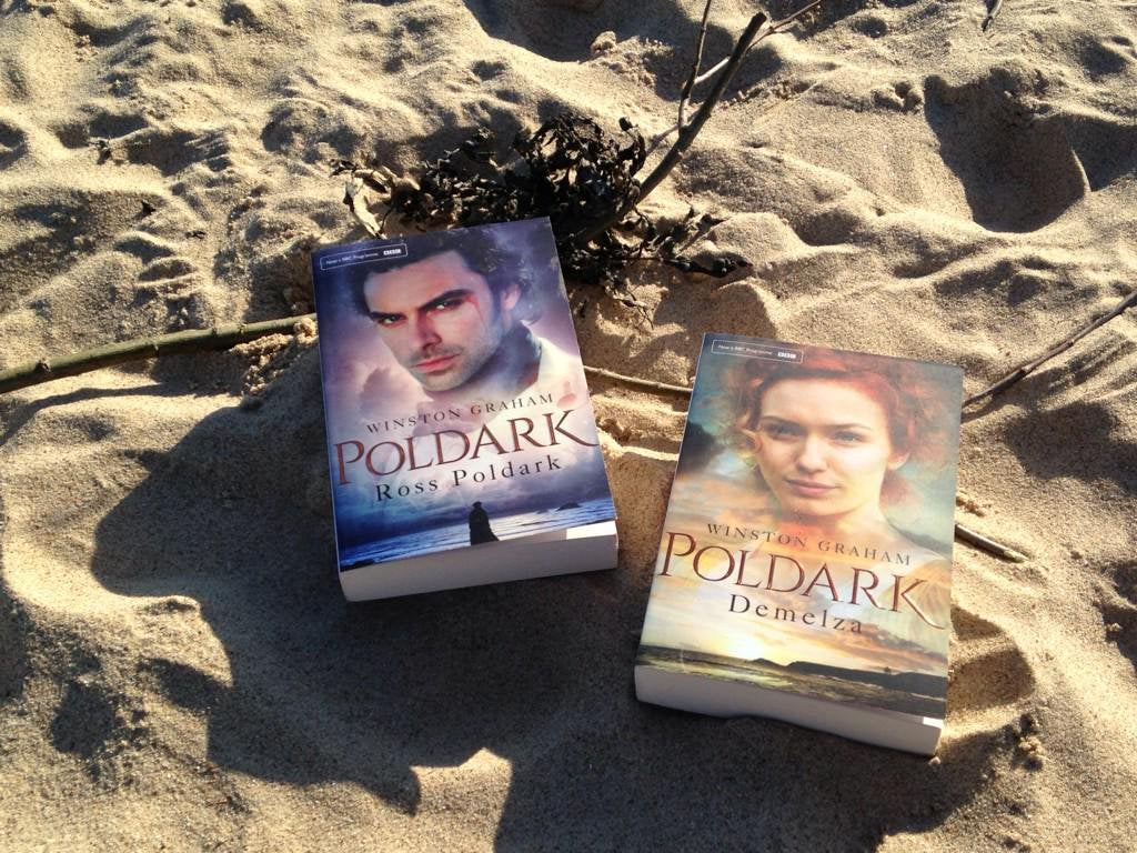 A picture of the books Ross Poldark and Demelza on the sand