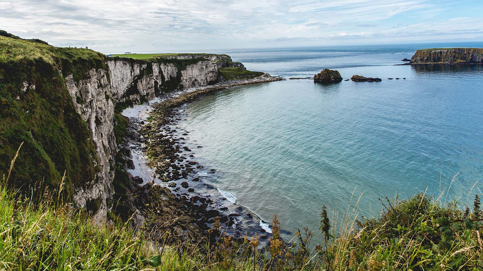 A photo of the rugged Irish coastline, showing a rocky beach and crystal blue waters