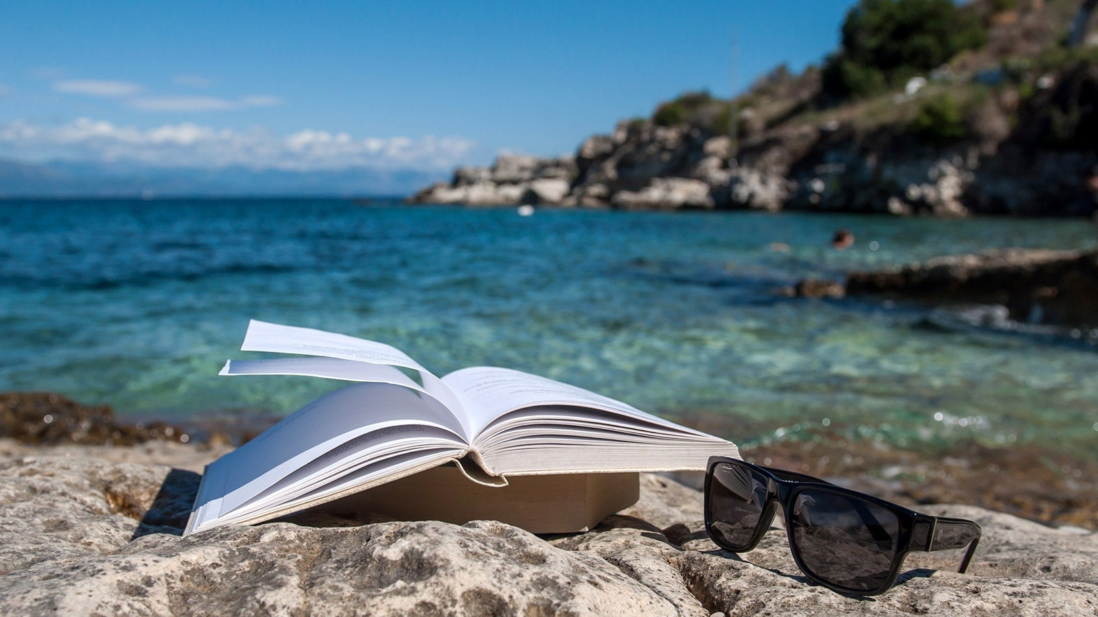 Book open next to sunglasses in front of blue sea