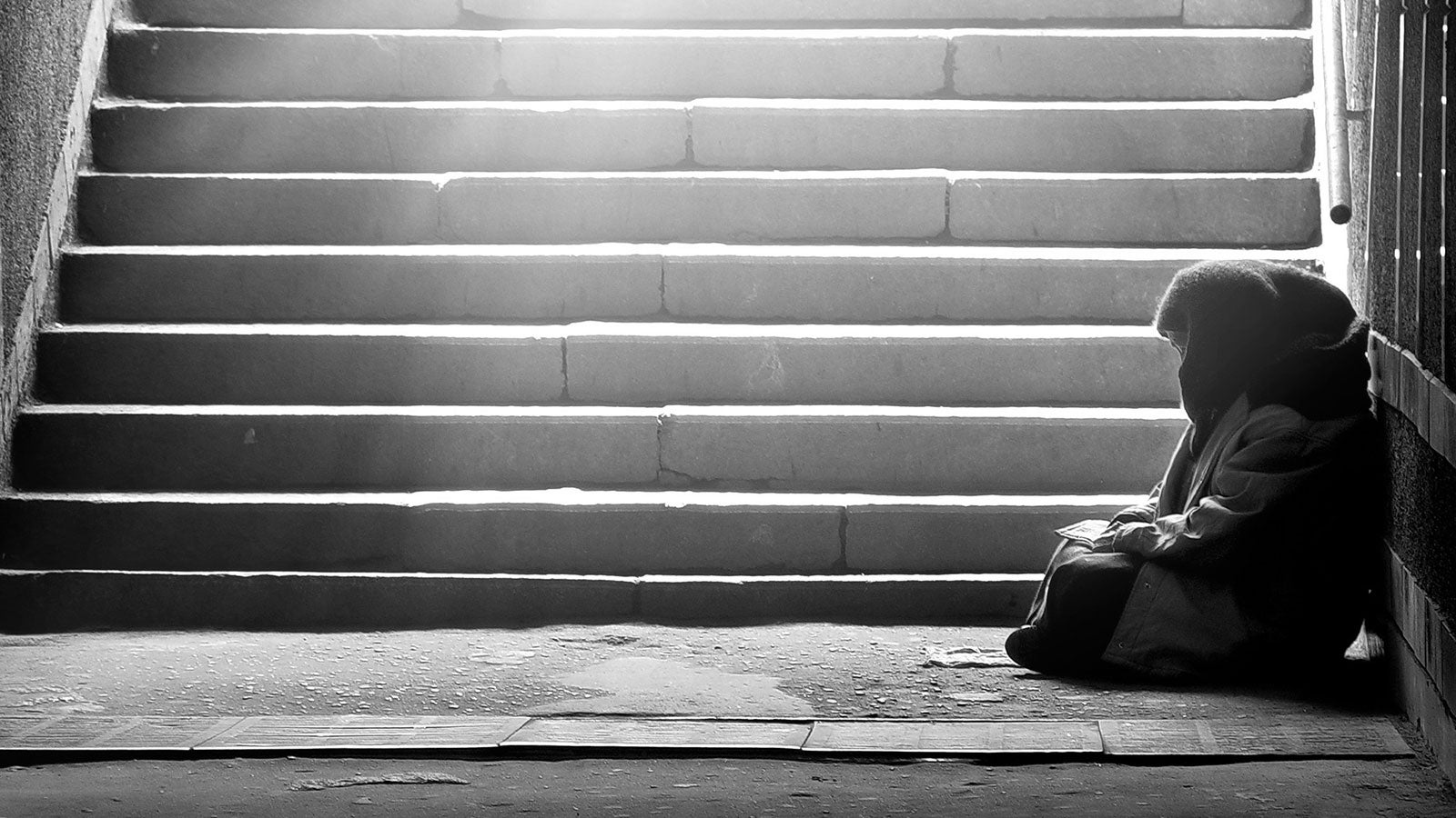 Black and white photo of a homeless woman sat at the bottom of some steps.