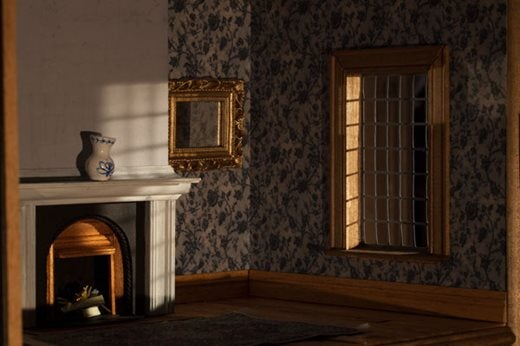 Tiny room including a small fireplace with a blue & white vase on the mantel, a small gold mirror and a window complete with small panes