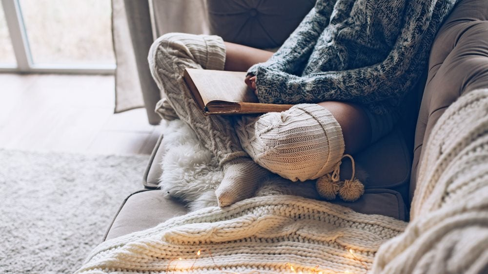 Person sitting on a sofa wearing knitted jumper and socks reading